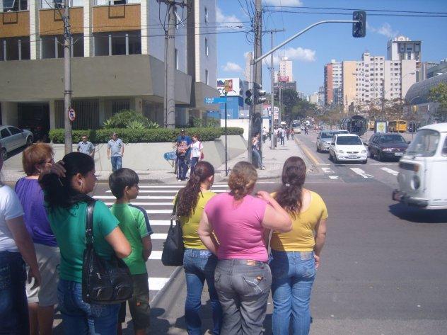 Pessoas sem carro aguardam o carro passar, mesmo com o sinal verde